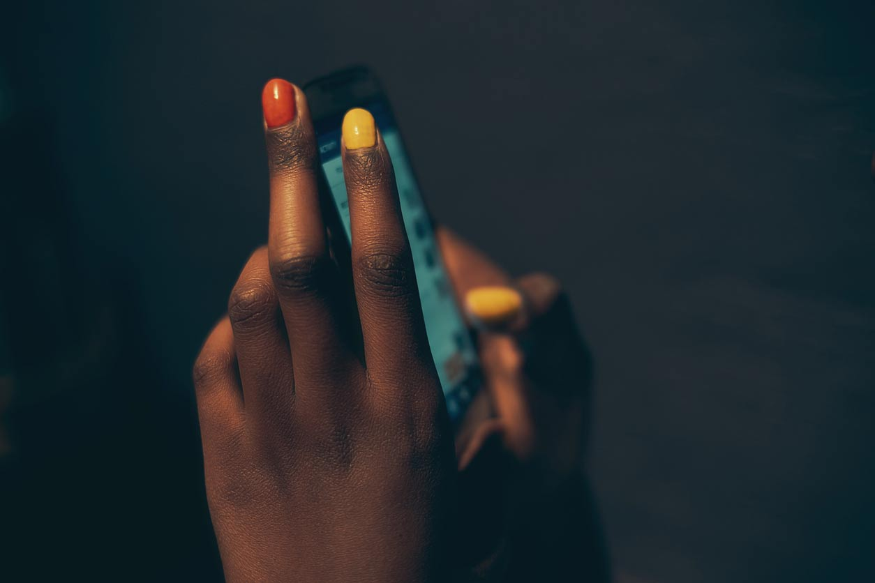 finger nails painted and holding a phone
