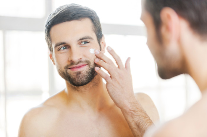 man apply sunscreen