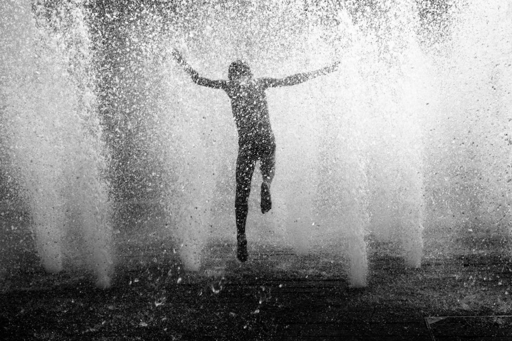 Child jumping in fountain